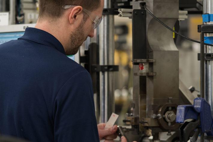 man with navy blue shirt working in machine shop