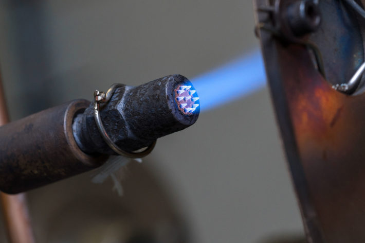 blue flame being projected onto metal component to test its coating